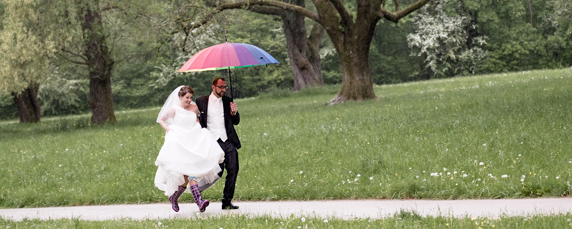 Das Foto zeigt ein Brautpaar im Laufschritt auf einem Kiesweg im Park, einen bunten Regenschirm in der Hand