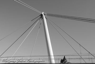 Die Fotografie zeigt einen Radfahrer auf einer Brücke, von unten fotografiert und viele Kabel und Stahlgeländer vor dem Himmel freigestellt
