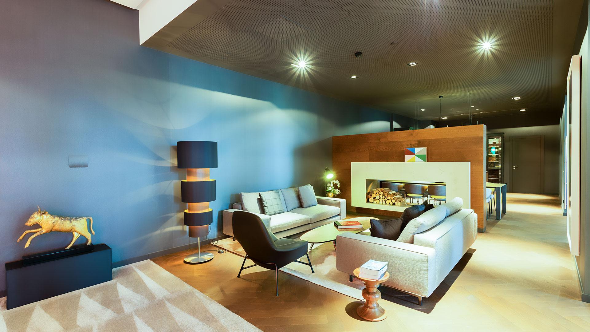 Eine Fotografie des wohnzimmerähnlichen Empfangsbereiches einer Firma, ausgeleuchtet mit Deckenstrahlern