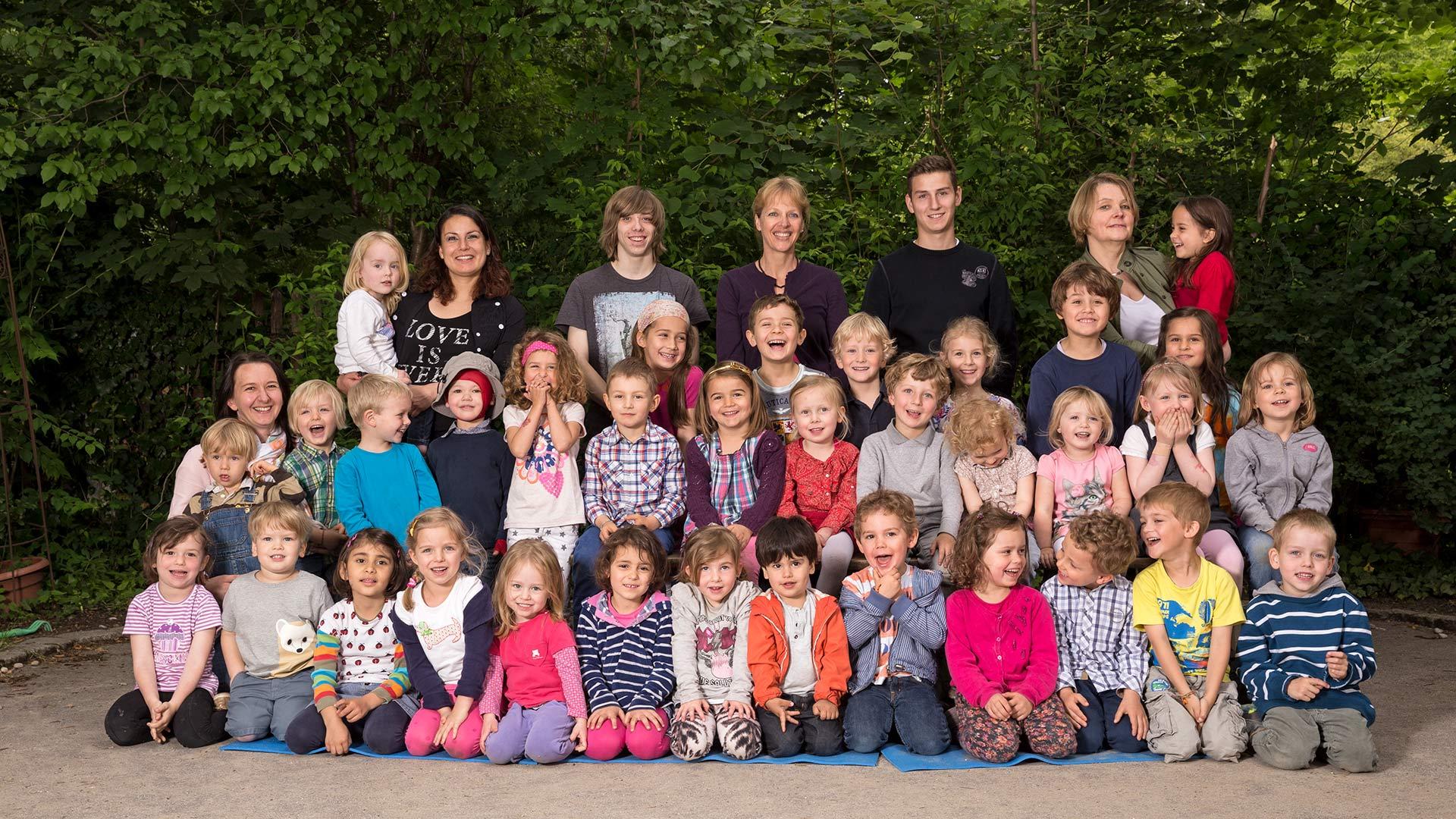 Die Fotografie zeigt die Kinder und Betreuerinnen und Betreuer im Freien vor einem grünen Hintergrund aus Blättern