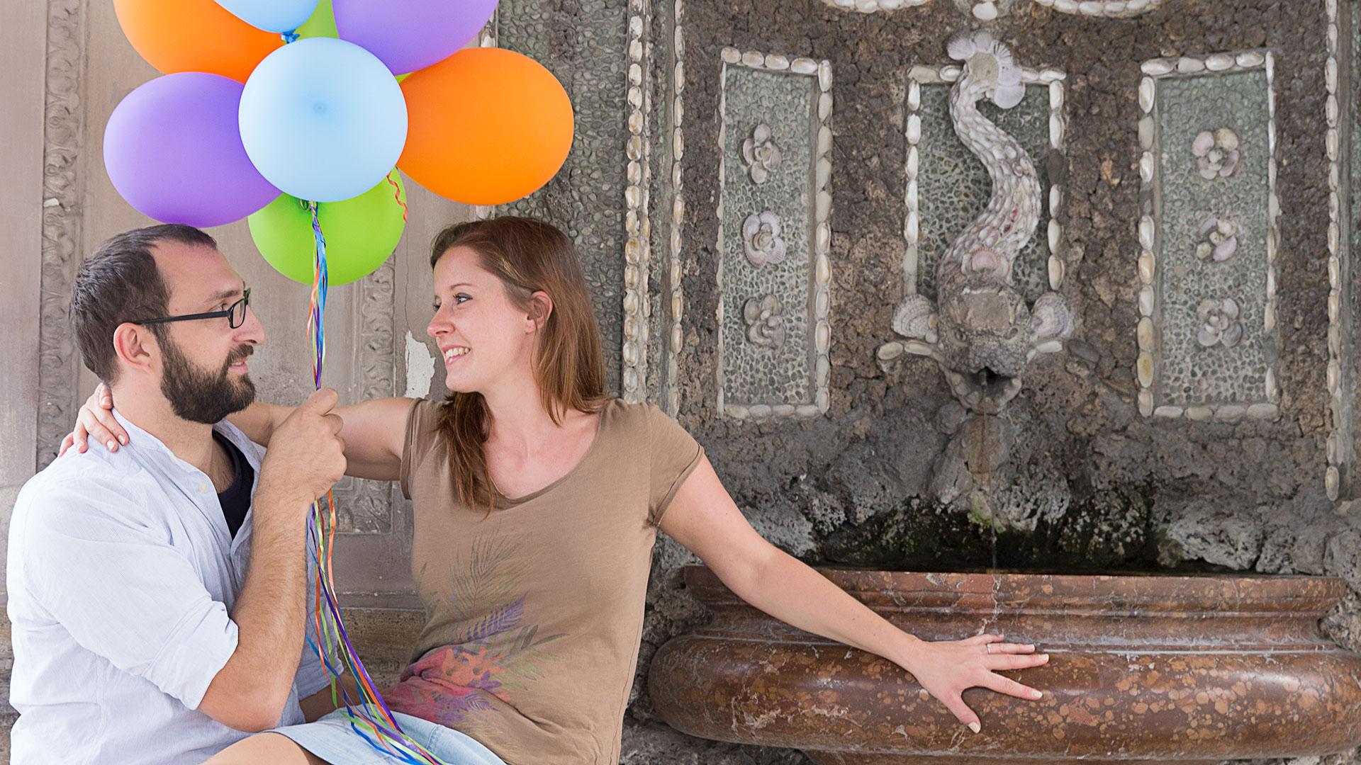 Fotografie mit einem jungen Paar, sie sitzt auf seinem Schoß und über ihren Köpfen Luftballons