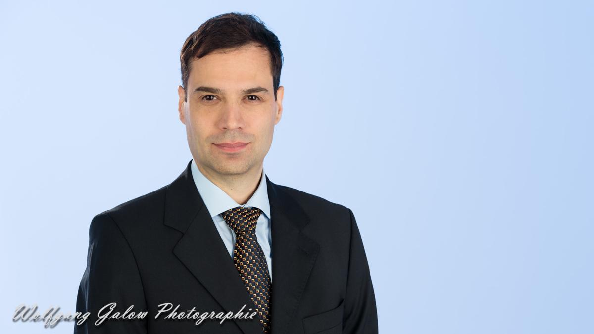 Bewerbungsfoto eines Mannes im dunklen Anzug mit blauem Hemd und Krawatte vor hellblauem Hintergrund