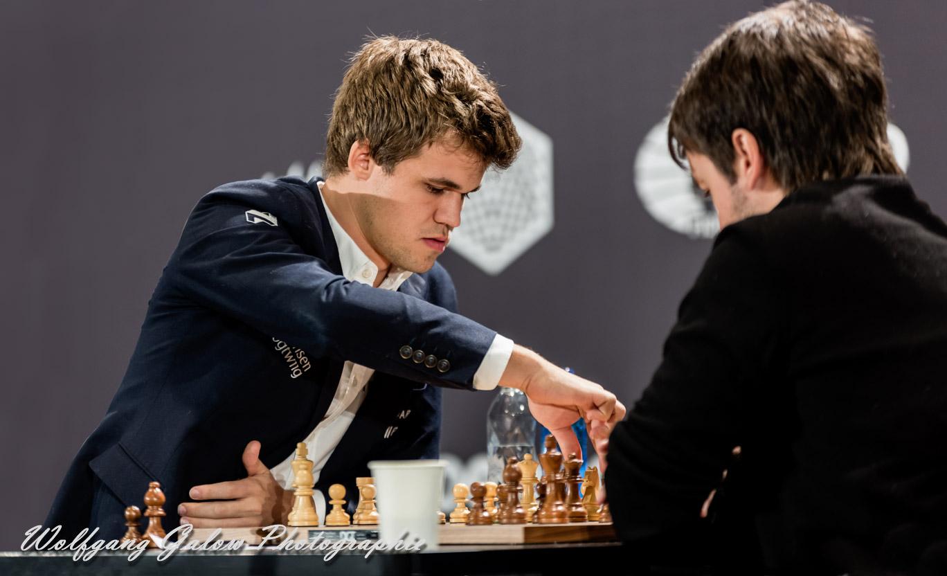 Das Foto zeigt den amtierenden Schachweltmeister Magnus Carlsen, während er einen Zug auf dem Schachbrett ausführt